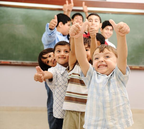 Children at school classroom with thumbs up. Source: Shutterstock
